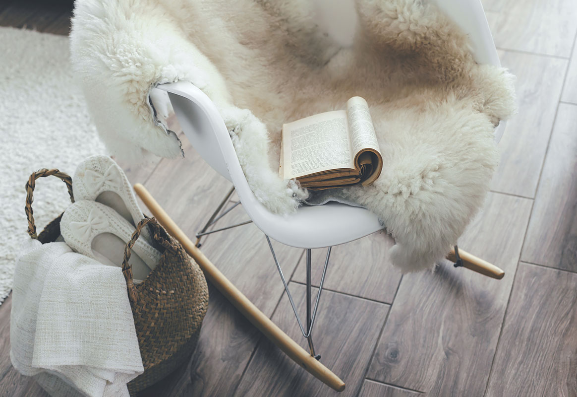 Still life details of living room. Sheep skin rug on modern armchair. Reading book on the rocket chair. Cozy winter scene in scandinavian interior.