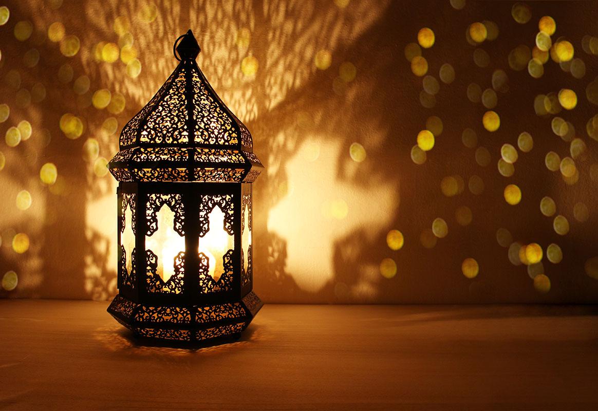 Ornamental Arabic lantern with burning candle glowing at night and glittering golden bokeh lights. Festive greeting card, invitation for Muslim holy month Ramadan Kareem, dark background.